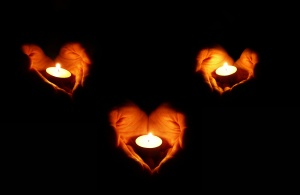 three couples of heart-shaped palms with candles