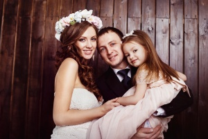 Beautiful pregnant woman in wedding dress and her husband are holding pretty cheerful daughter in arms at a plank wall background. Concept of happy family.