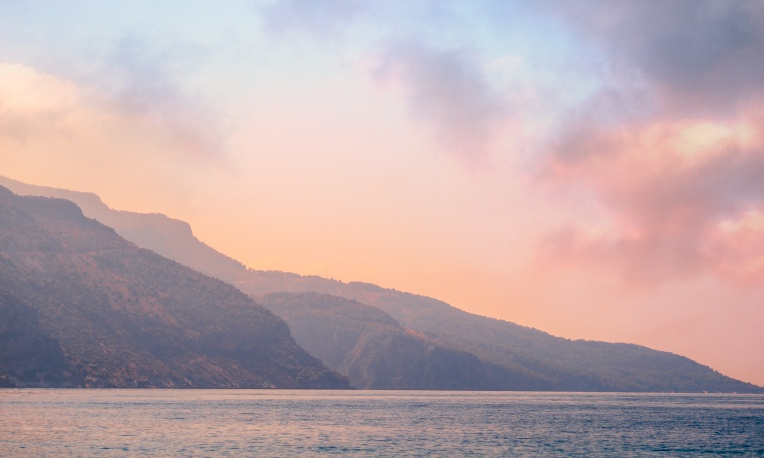Mountains landscape on the coast at sunrise - serenity and rose quartz colors.